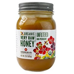 A photo of a jar of raw organic honey that can be used to whiten armpits.