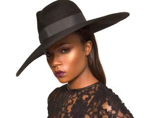 A image of a young dark skinned woman wearing a large hat to protect against the sun.
