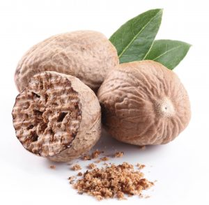 An image of nutmeg sliced open with leaves to demonstrate its use for face lightening and skin spot remover